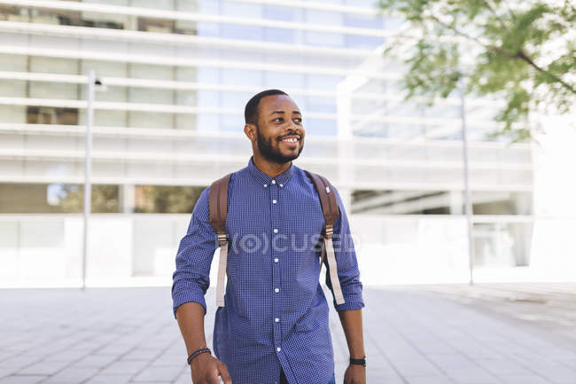 Portrait of smiling afro man with backpack in city street — Stock Photo
