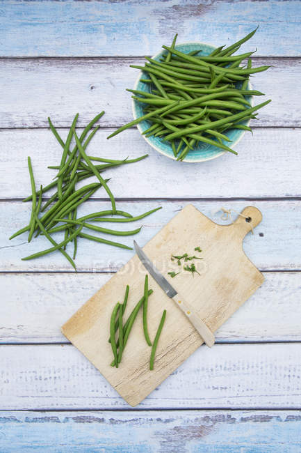 Fresh green beans in bowl and on wooden chopping board on white wood — Stock Photo