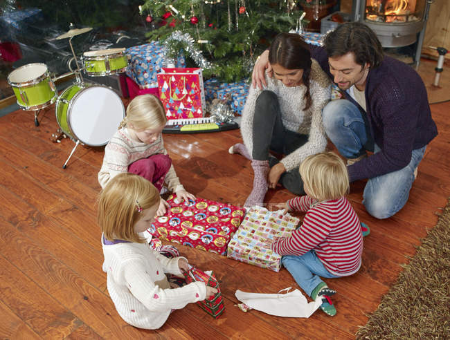 Family unwrapping Christmas presents, overhead view — Stock Photo