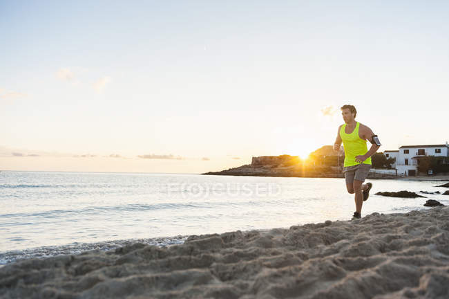 Young man jogging on beach in morning — Stock Photo