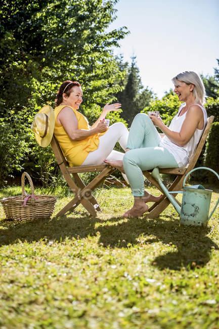 Щасливі зрілих жінок, сидячи на стільці галявині в саду — стокове фото