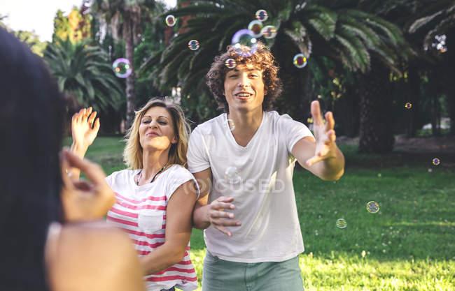 Молодые счастливые друзья веселятся и играют с мыльными пузырями в парке — стоковое фото
