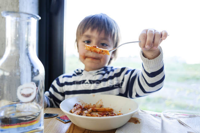 Boy eating pasta with tomato sauce at kitchen — Stock Photo