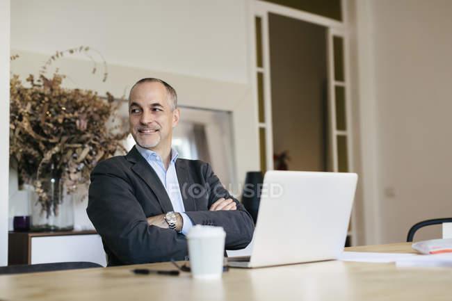 Успішний бізнесмен, сидячи за столом з ноутбуком і дивиться вбік — стокове фото