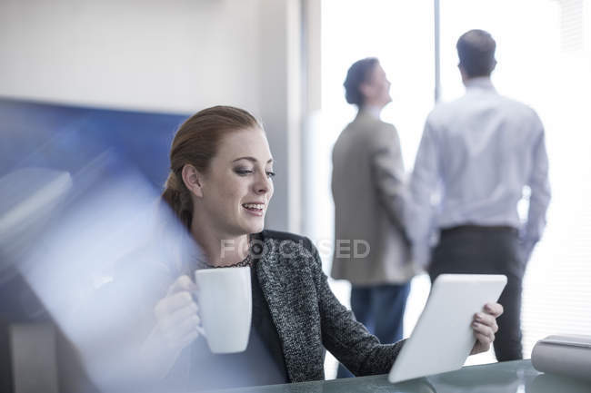 Smiling woman in office holding cup of coffee and digital tablet — Stock Photo