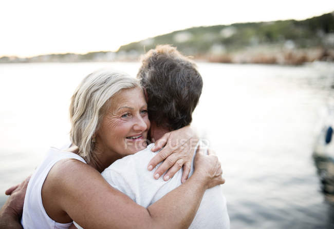 Happy senior woman hugging her husband in front of the sea — Stock Photo