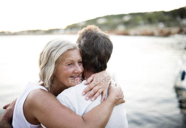 Felice donna anziana abbracciare il marito di fronte al mare — Foto stock
