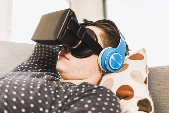 Joven con gafas 3D tumbado en el couich en casa - foto de stock