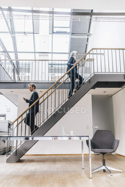 Businesswoman and businessman walking on stairs in a loft — Stock Photo