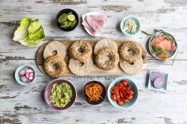 Colazione, ciambelle (bagels), verdure, salmone e prosciutto — Foto stock