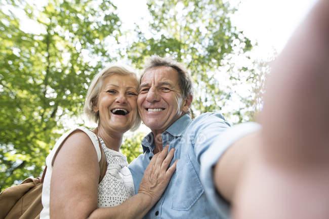 Активні милий старший пара обіймати і беручи selfie в парку — стокове фото