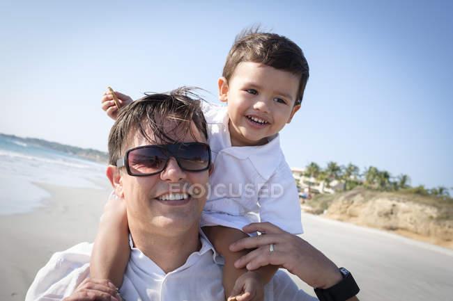 Portrait du père portant son fils sur les épaules à la plage — Photo de stock
