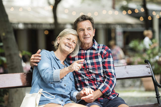 Happy senior couple hugging each other on bench at park — Stock Photo
