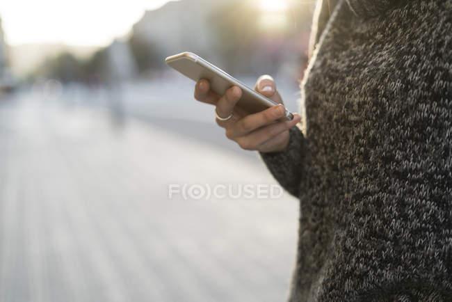 Close-up da mão feminina, usando telefone celular ao ar livre — Fotografia de Stock