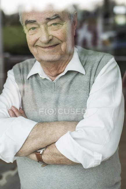 Portrait de sourire senior homme avec bras croisés en regardant par la fenêtre — Photo de stock