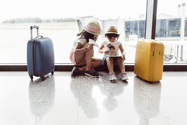 Duas meninas esperando no aeroporto, brincando com tablet digital — Fotografia de Stock