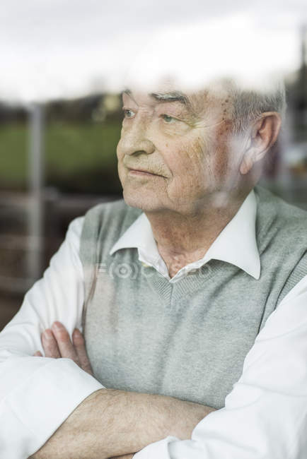 Portrait de songeur senior homme avec bras croisés en regardant par la fenêtre — Photo de stock