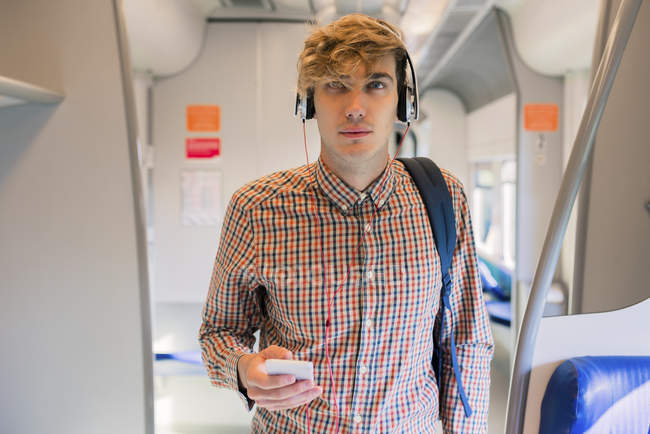 Young man listening music with headphones standing in a train — Stock Photo