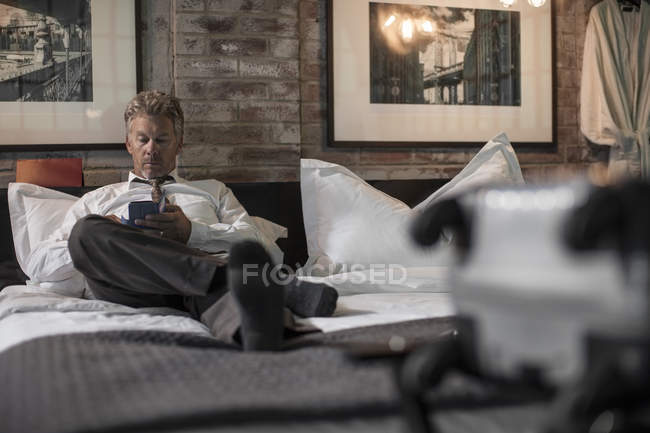 Businessman using smartphone on bed in hotel room — Stock Photo