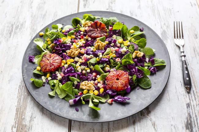Wintersalat, Feldsalat, Rotkohl, Mais, Fetakäse, Blutorange, Walnüsse und Granatapfelkerne — Stockfoto