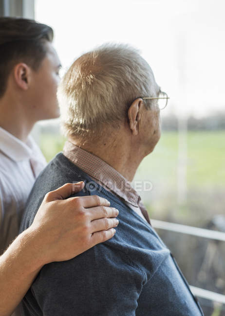 Senior man and geriatric nurse looking through window — Stock Photo