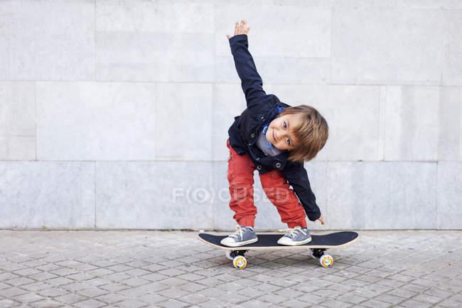 Портрет маленький хлопчик, балансуючи на скейтборді — стокове фото