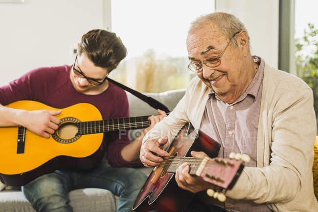 Senior spielt zu Hause mit Enkel Gitarre — Stockfoto