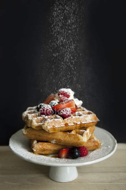 Carrinho do bolo de waffles belgas com diferentes frutas polvilhadas com açúcar de confeiteiro — Fotografia de Stock