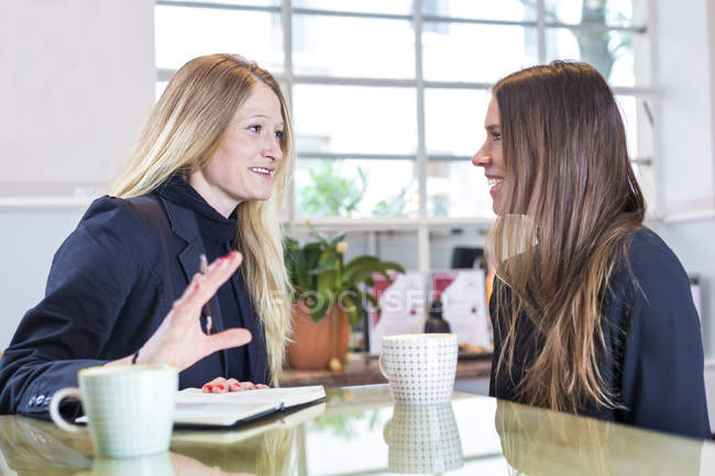 Two businesswomen sitting with cups of coffee in cafe and talking — Stock Photo
