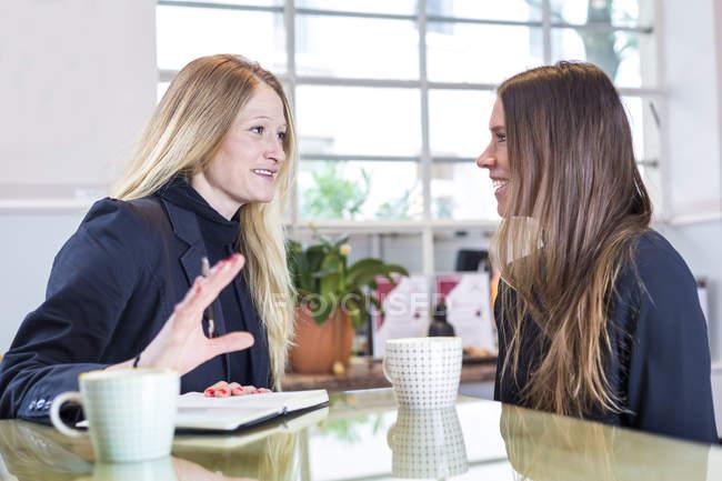 Zwei Geschäftsfrauen mit Tassen Kaffee im Café sitzen und reden — Stockfoto
