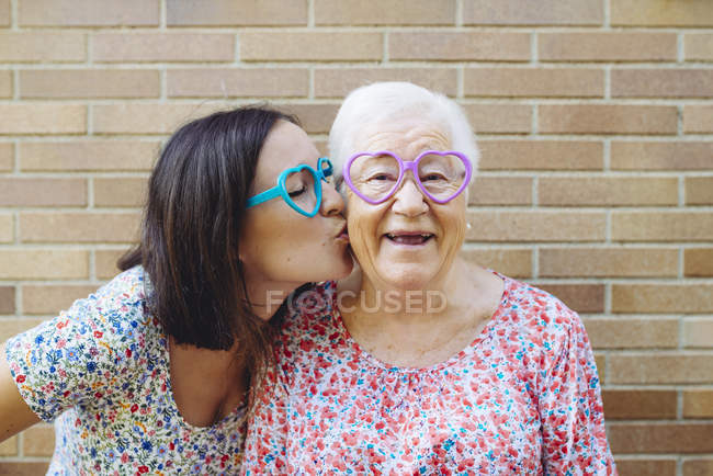 Happy granddaughter and grandmother wearing heart-shaped glasses — Stock Photo
