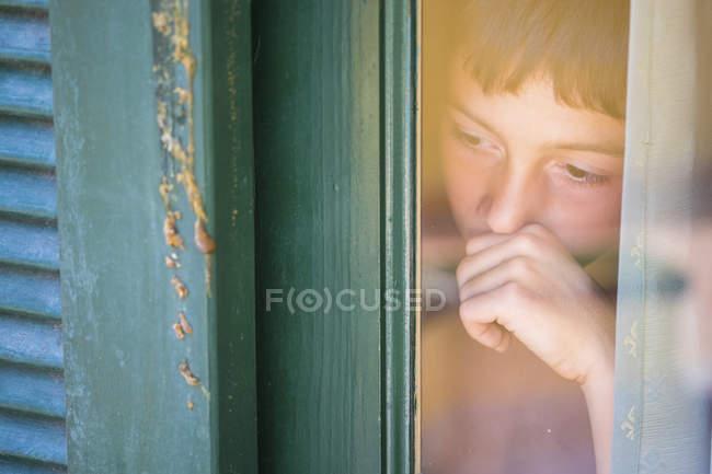 Portrait of boy looking through wondow — Stock Photo