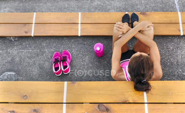 Top view of sportswoman resting in an athletics stadium — Stock Photo