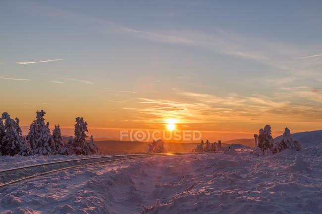 Germany, Saxony-Anhalt, Harz National Park, Brocken, rail tracks of Harz Narrow Gauge Railway in winter against the evening sun — Stock Photo