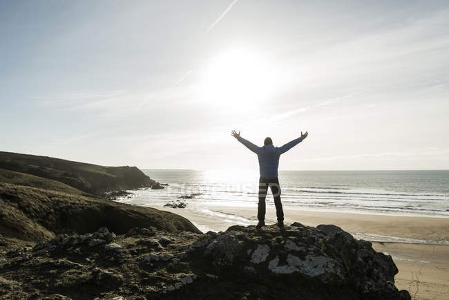 Man standing on rock at the coast with outstretched arms — Stock Photo