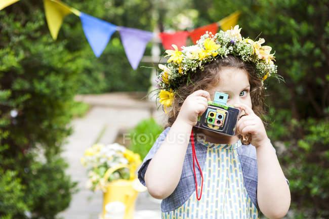 Маленька дівчинка носіння квіти фотографування з vintage камери — стокове фото