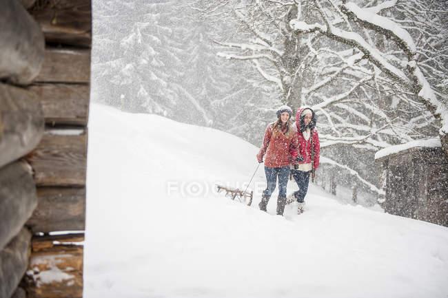Dos mujeres jóvenes con trineo en nieve pesada - foto de stock