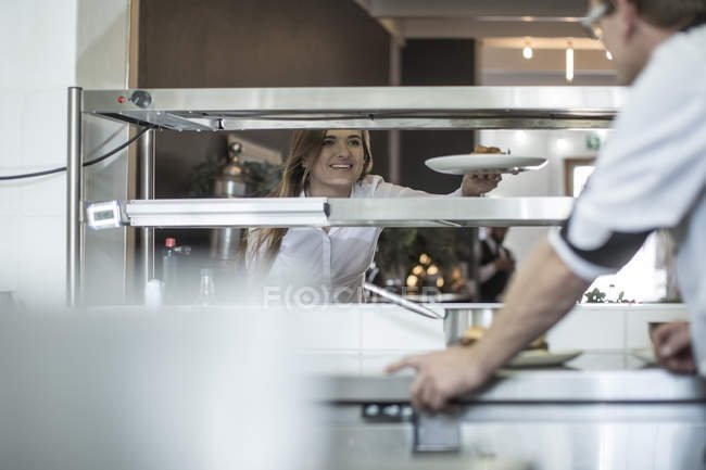 Waiter picking up food from the kitchen of modern restaurant — Stock Photo