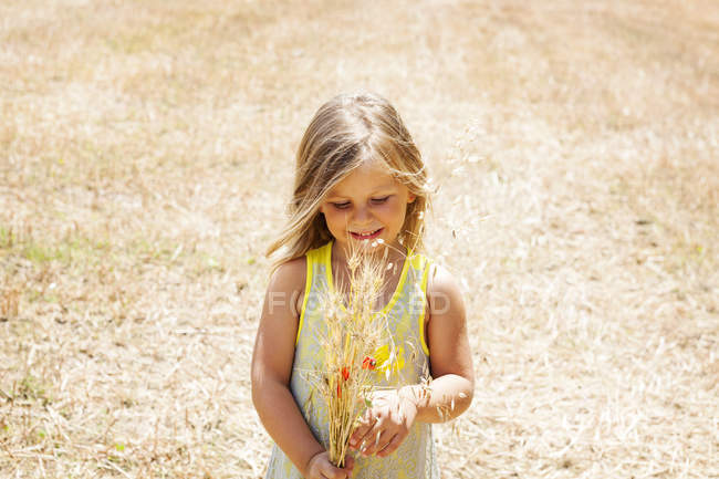 Portrait of little girl with bunch of flowers on a meadow — Stock Photo