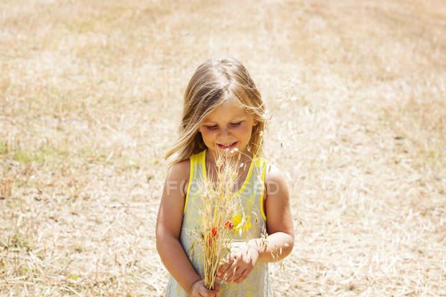 Retrato de menina com ramo de flores em um prado — Fotografia de Stock