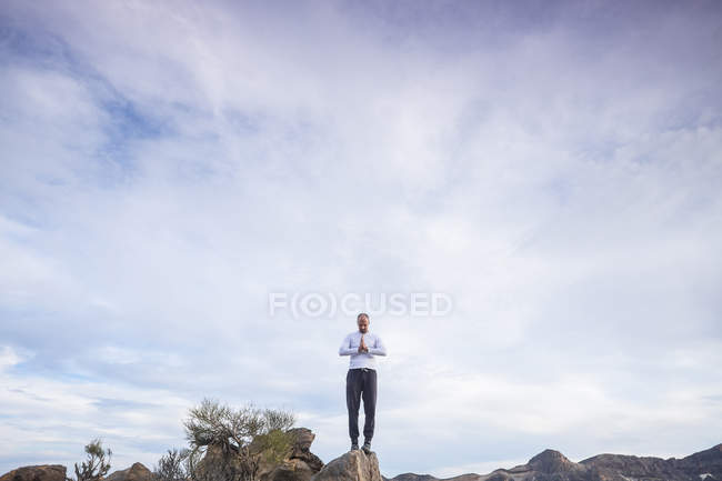Spain, Tenerife, man in prayer position standing on a rock — Stock Photo