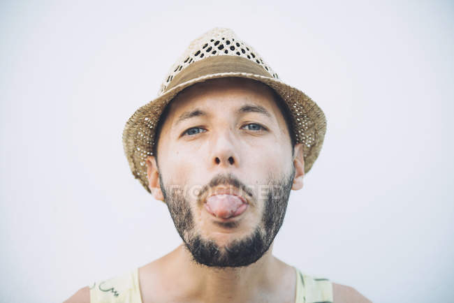 Portrait of bearded man with straw hat sticking out tongue in front of light background — Stock Photo