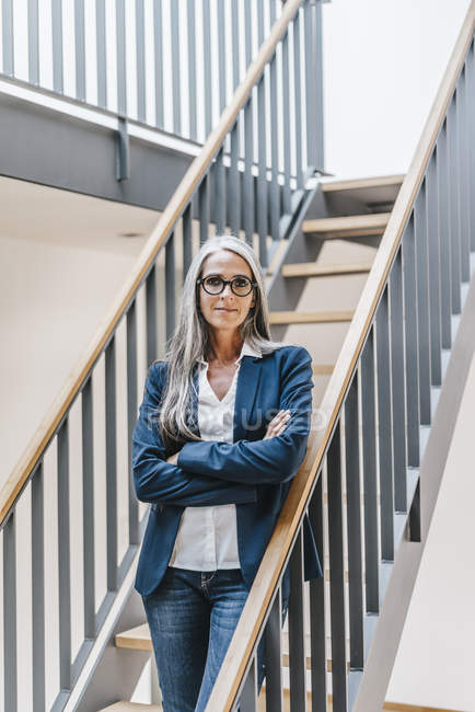 Confident businesswoman with long grey hair standing on stairs in office — Stock Photo
