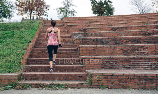 Vue arrière de la femme sportive montant les escaliers — Photo de stock
