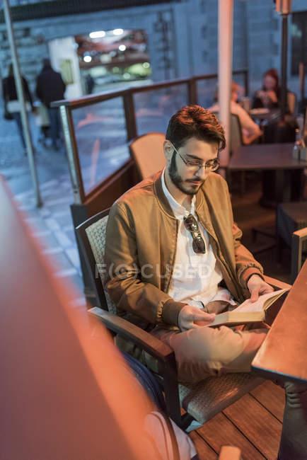 Junger Mann, ein Buch an Bar im freien — Stockfoto