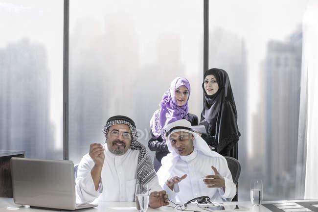 Deux hommes d'affaires du Moyen-Orient ayant une vidéoconférence, assistantes en arrière-plan — Photo de stock