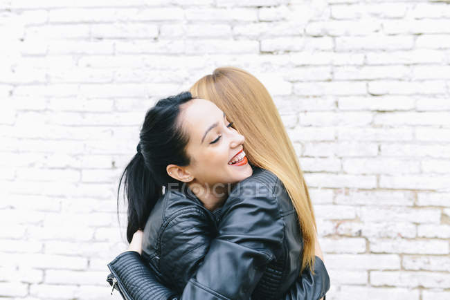 Due giovani donne che si abbracciano davanti al muro di mattoni bianchi — Foto stock