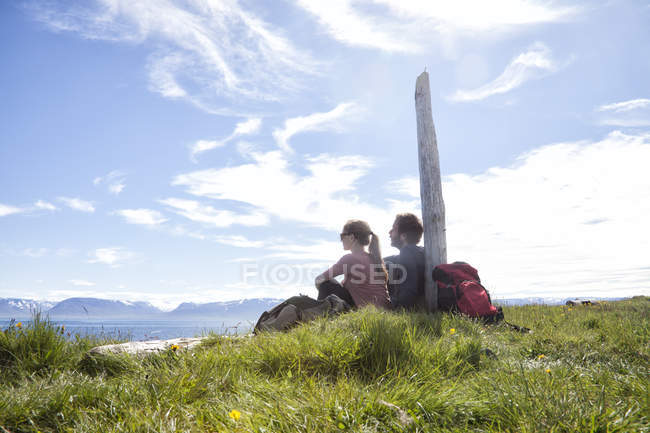 Iceland, hiking couple resting on a meadow looking at view — стокове фото