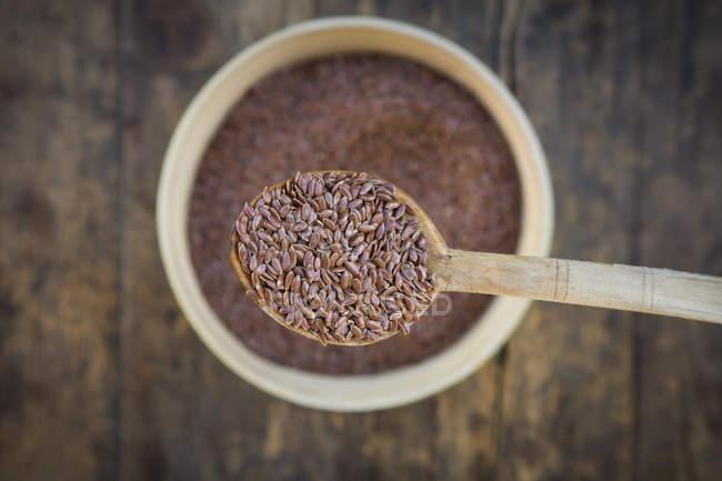Chiuda in su del cucchiaio di legno di semi di lino biologico — Foto stock