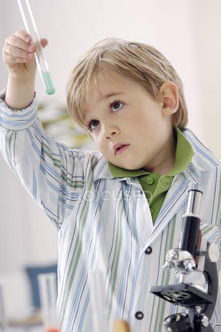 Портрет мальчика с пробиркой и микроскопом — стоковое фото